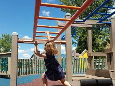 Girl swinging on monkey bars at Oconomowoc Imagination Station on the weekend things to do
