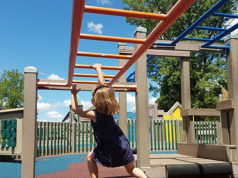 Girl swinging on monkey bars at Oconomowoc Imagination Station on the weekend things to do